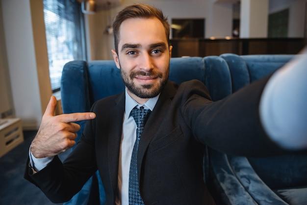 Красивый молодой взволнованный бизнесмен в костюме, сидя в вестибюле отеля, используя мобильный телефон, принимая селфи, указывая