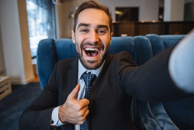Красивый молодой взволнованный бизнесмен в костюме, сидя в холле отеля, используя мобильный телефон, принимая селфи