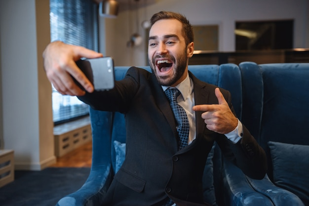 Handsome young excited businessman wearing suit sitting at the hotel lobby, using mobile phone, taking a selfie, pointing