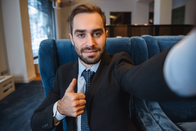 Handsome young excited businessman wearing suit sitting at the hotel lobby, using mobile phone, taking a selfie