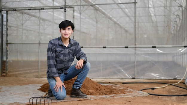 Handsome young farmer in plaid shirt and jeans sitting near a pile of soil for planting in greenhouse.