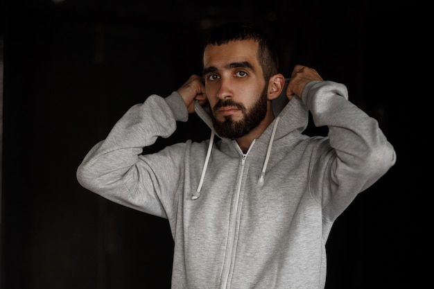 Handsome young fashion man with beard in gray hoodie against dark wall