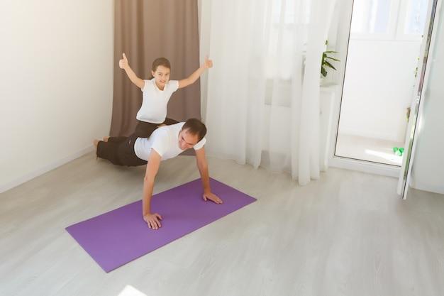 ハンサムな若い父親と彼のかわいい小さな娘は、自宅の床でレッグレイズとリバース板をやっています。家族のフィットネストレーニング。