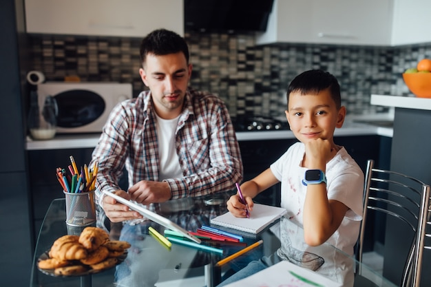 ハンサムな若い父と彼の息子は教育のためにデジタルタブレットを使用し、彼がレッスンを学ぶのを助けます