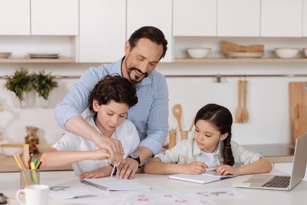 Красивый молодой отец помогает своему сыну начертать круг с помощью циркуля, направляя его руку, в то время как его дочь пристально смотрит на нее