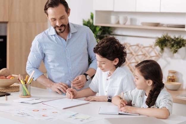 그의 사랑스러운 딸이 메모를 만드는 동안 노트북에서 합계를하고 그의 지능형 작은 아들을보고 잘 생긴 젊은 아버지