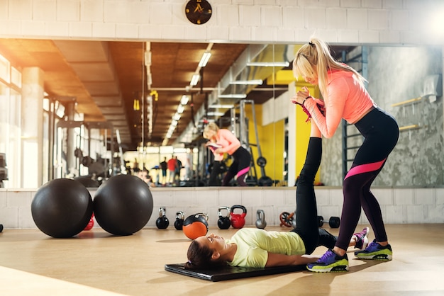 Handsome young female instructor helping her client to stretch her legs after hard training in a gym.