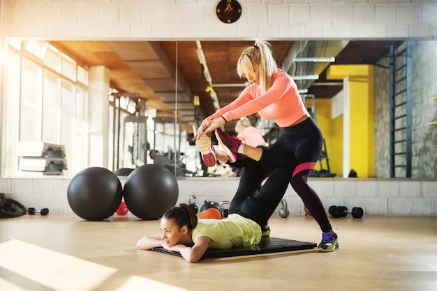 ジムでのハードトレーニングの後に彼女のクライアントが彼女の足を伸ばすのを助けるハンサムな若い女性インストラクター。