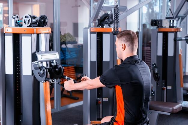 フィットネスセンターのジムルームでモダンなローイングマシンでトレーニングするハンサムな若いフィット男