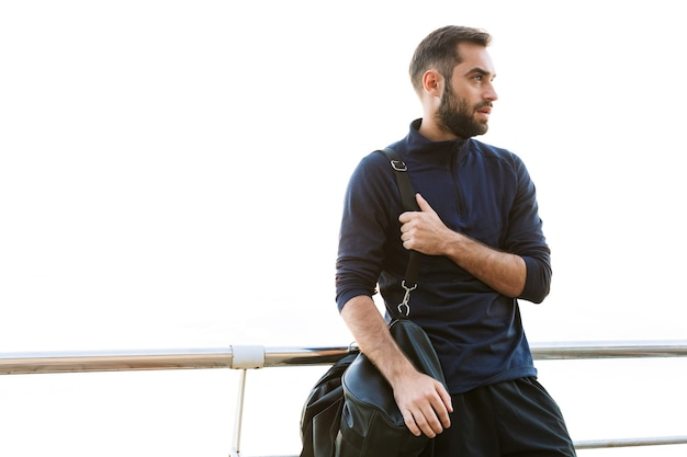 Красивый молодой здоровый спортсмен с сумкой, стоящей на открытом воздухе