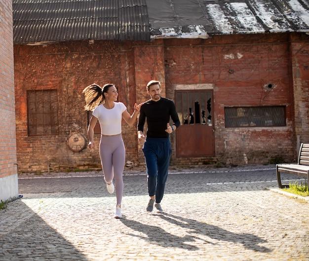都市部で実行されているハンサムな若いフィットネスカップル