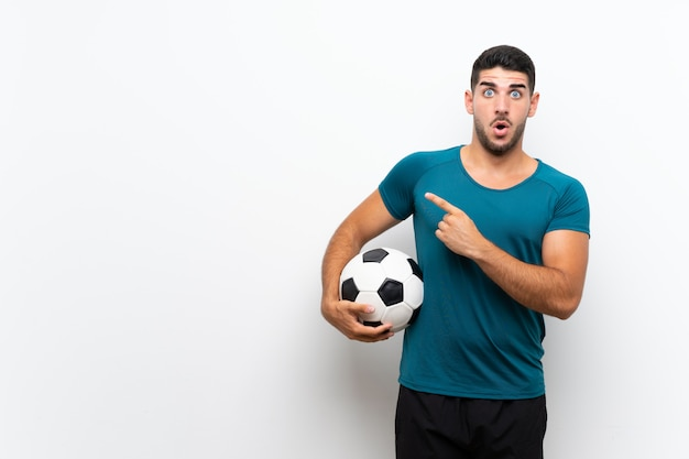 Handsome young football player man over isolated white wall surprised and pointing side
