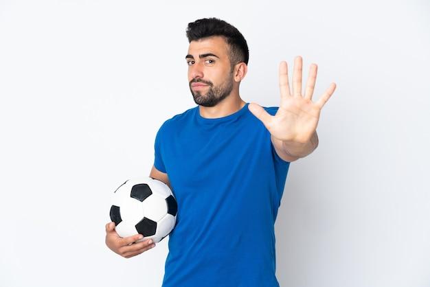 손가락으로 5 세 고립 된 벽 위에 잘 생긴 젊은 축구 선수 남자