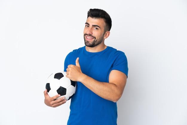 親指を立てるジェスチャーを与える孤立した壁の上のハンサムな若いサッカー選手の男