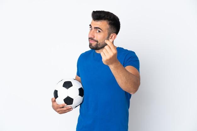 お金のジェスチャーを作る孤立した壁の上のハンサムな若いサッカー選手の男