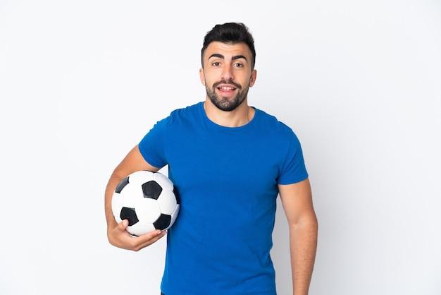 엉덩이에 팔을 포즈와 미소 격리 된 벽 위에 잘 생긴 젊은 축구 선수 남자