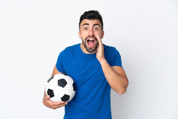 Красивый молодой футболист мужчина над изолированной стеной с удивленным и шокированным выражением лица