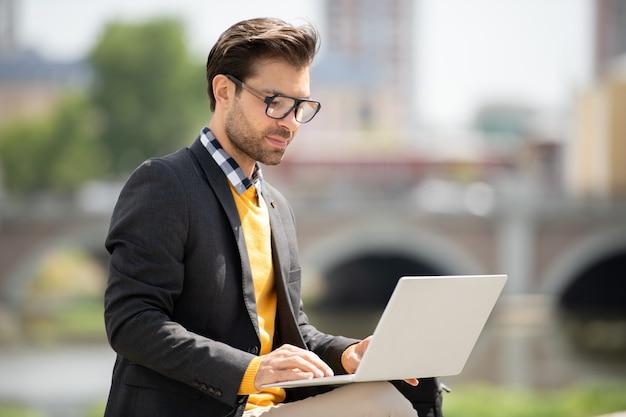 屋外でオンライン情報を検索しながらノートパソコンのディスプレイを見てスマートカジュアルウェアでハンサムな若いフリーランサー