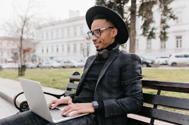 公園でコンピューターを操作するハンサムな若いフリーランサー。ベンチでラップトップで勉強している帽子をかぶったうれしいアフリカ人の屋外の肖像画。