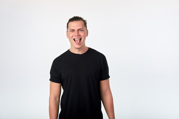 Handsome young funny stylish cheerful man wearing a black cotton short-sleeved t-shirt have fun, showing tongue, posing .