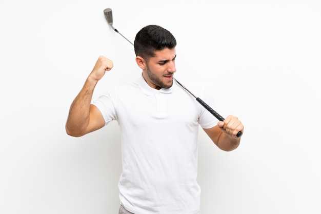 Handsome young golfer player man over isolated white wall celebrating a victory