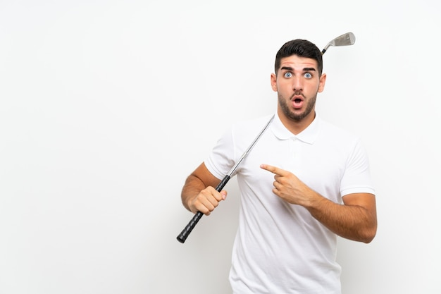 Handsome young golfer player man over isolated white wall surprised and pointing side