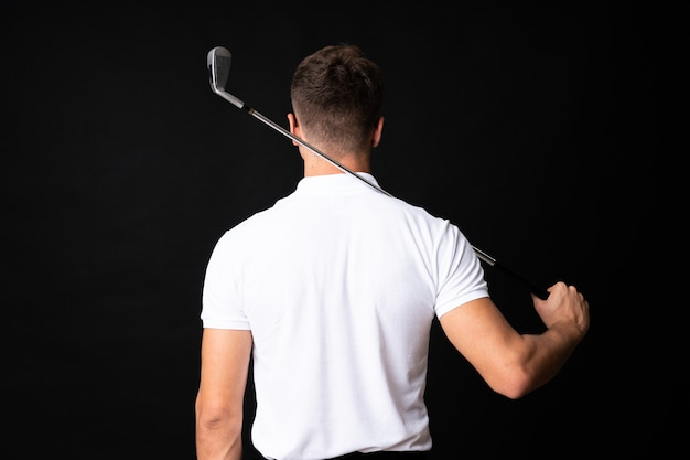 Handsome young golfer player man over isolated