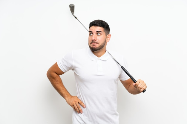 Handsome young golfer player man  on white  making doubts gesture while lifting the shoulders
