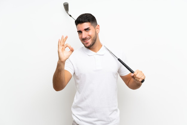 Handsome young golfer player man  on white  showing ok sign with fingers