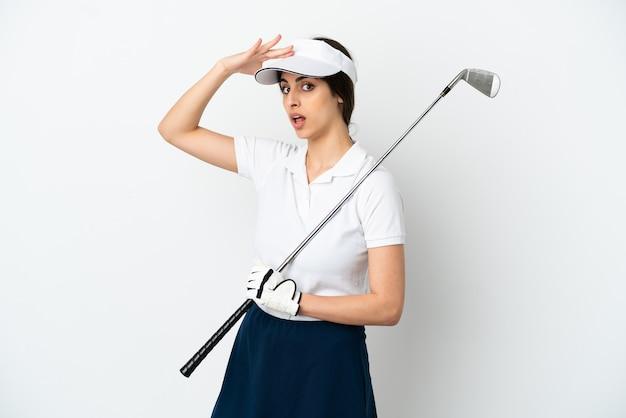 Красивая молодая женщина-игрок в гольф изолирована на белом фоне, делая неожиданный жест, глядя в сторону
