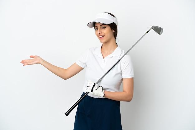 白い背景で隔離のハンサムな若いゴルファープレーヤーの女性は、来て招待するために手を横に伸ばします