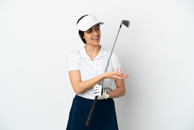 Красивая молодая женщина-игрок в гольф изолирована на белом фоне, протягивая руки в сторону для приглашения приехать
