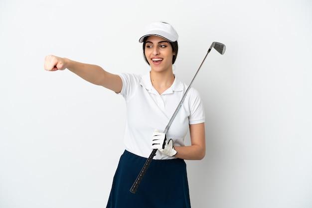 親指を立てるジェスチャーを与える白い背景で隔離のハンサムな若いゴルファープレーヤーの女性