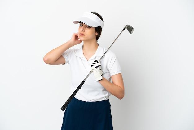 Красивая молодая женщина игрок в гольф изолирована на белом фоне с сомнениями