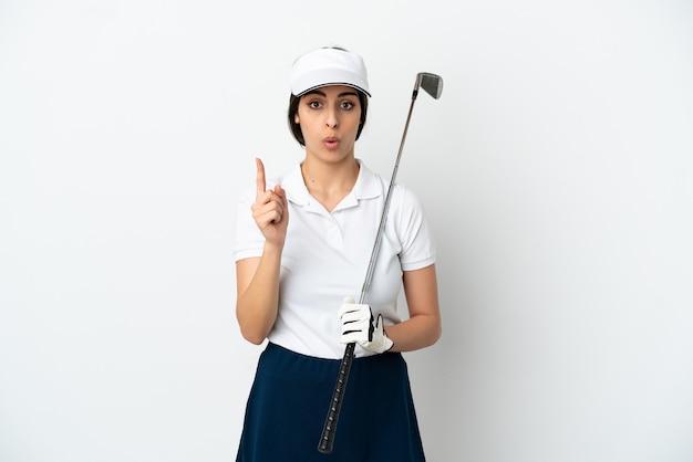 Красивая молодая женщина-игрок в гольф изолирована на белом фоне, намереваясь реализовать решение, подняв палец вверх