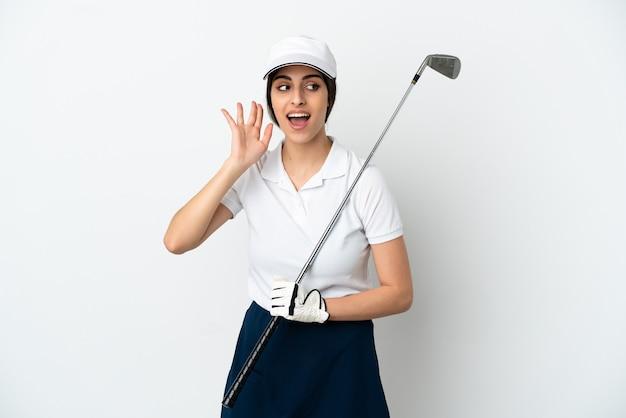 Красивая молодая женщина игрок в гольф изолирована на белом фоне, слушая что-то, положив руку на ухо