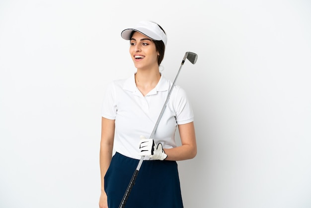 横を見て笑っている白い背景で隔離のハンサムな若いゴルファープレーヤーの女性