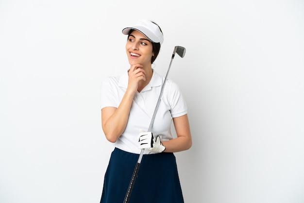 Красивая молодая женщина игрок в гольф, изолированные на белом фоне, глядя в сторону и улыбаясь
