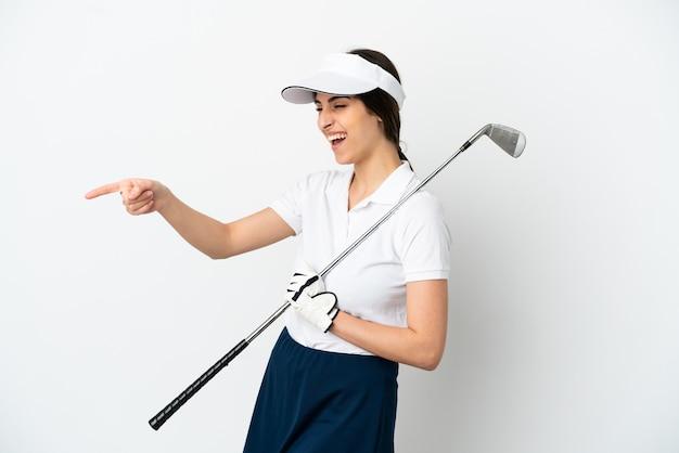 Красивая молодая женщина-игрок в гольф изолирована на белом фоне, указывая пальцем в сторону и представляет продукт