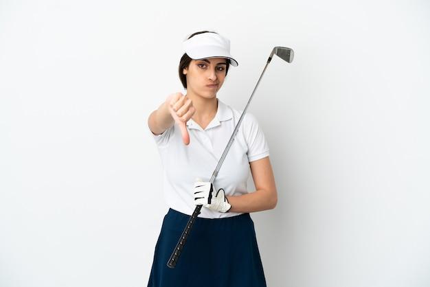 Красивая молодая женщина-игрок в гольф изолирована на белом фоне, показывая большой палец вниз с отрицательным выражением лица