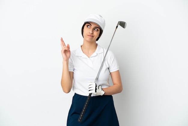 Красивая молодая женщина-игрок в гольф изолирована на белом фоне со скрещенными пальцами и желает лучшего