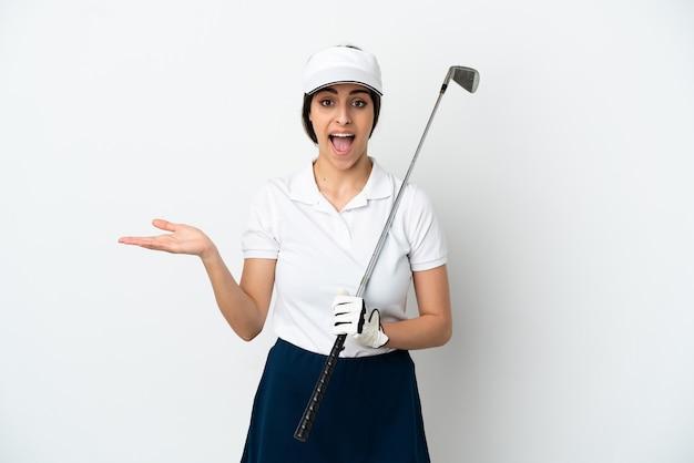 Красивая молодая женщина-игрок в гольф изолирована на белом фоне с шокированным выражением лица