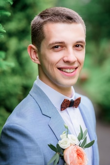 Handsome young groom in grey suit with orange boutonniere