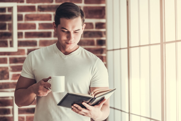 Handsome young guy holding cup with coffee.