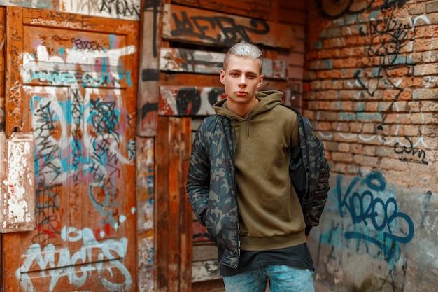 거리에서 벽 근처 세련된 군사 재킷에 잘 생긴 젊은 남자