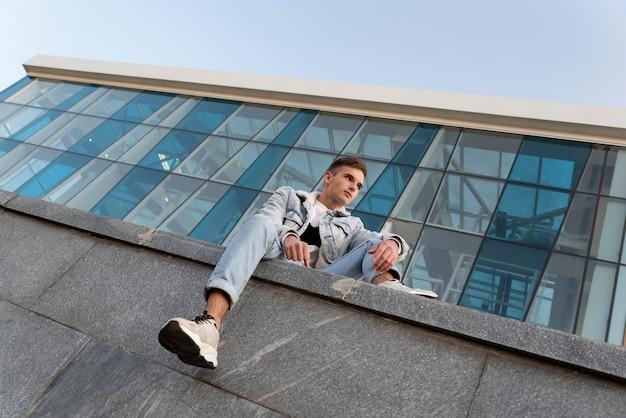 Красивый молодой парень в стильной одежде сидит на поверхности стеклянного фасада. студент отдыхает после учебы. вид снизу.