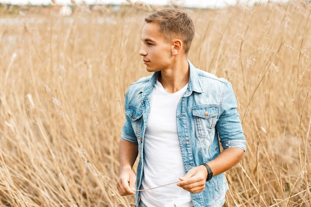 Handsome young guy in jeans clothes and a white t-shirt is walking outdoors in the grass