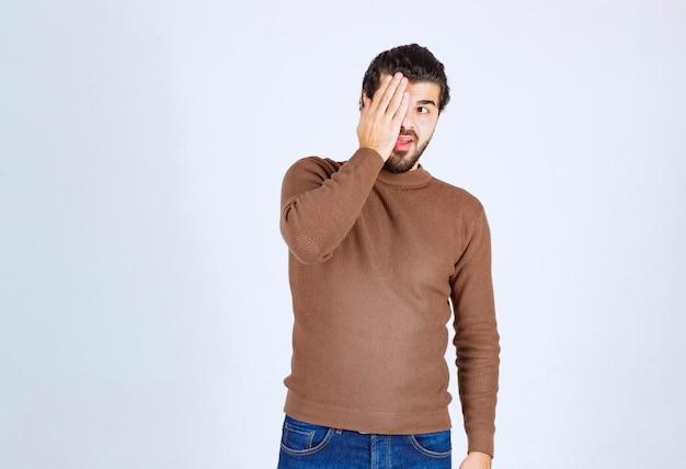 手で目を覆うハンサムな若い男のモデル。