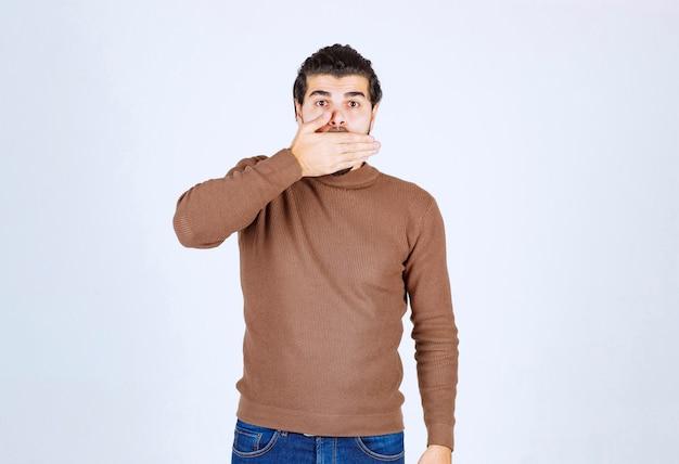 手で口を覆うハンサムな若い男のモデル。