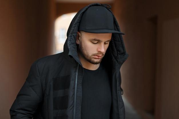 검은 세련된 야구 모자와 겨울 재킷이 거리에서 포즈를 취하는 후드에 잘 생긴 젊은 남자 모델
